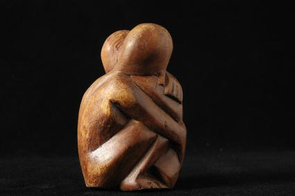 Wood sculpture of two people hugging | Therapist Denver CO